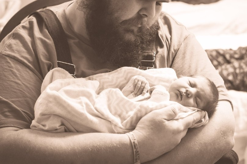Father holding newborn in hospital portrait